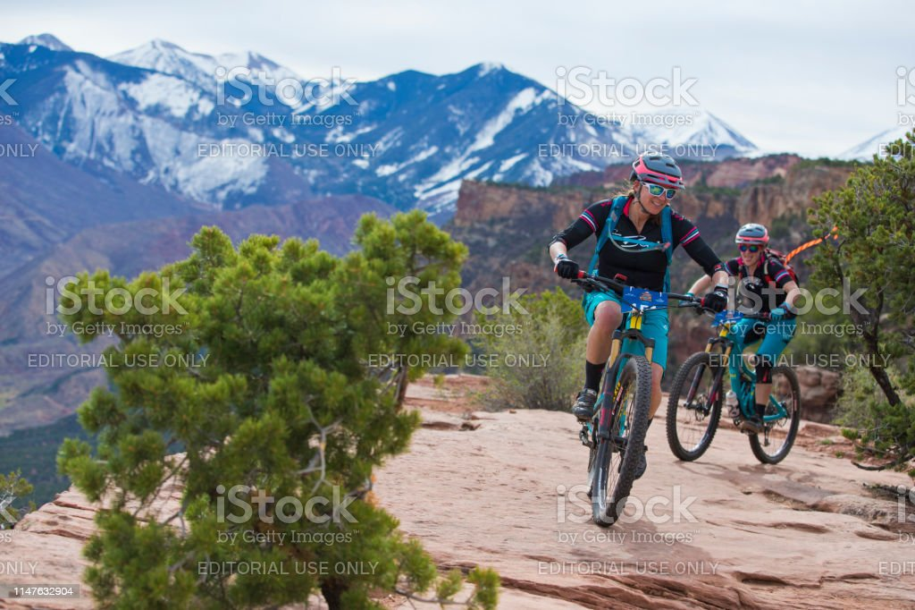 Two women ride down Porcupine Rim Trail during the Moab Rocks...