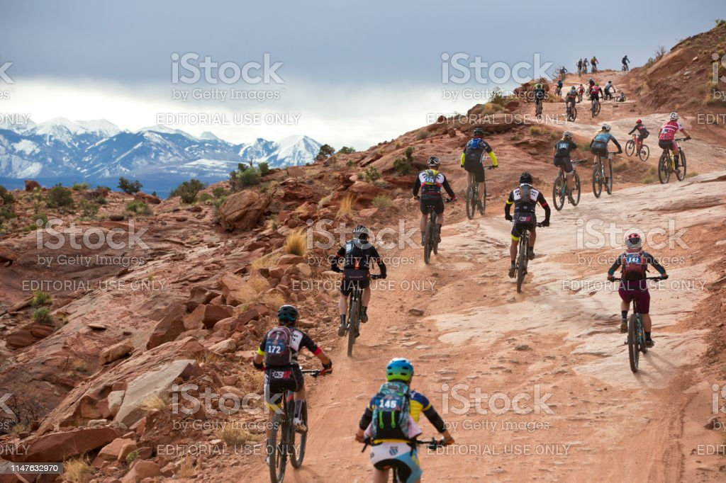 Racers head up the first hill during the Moab Rocks mountain bike...