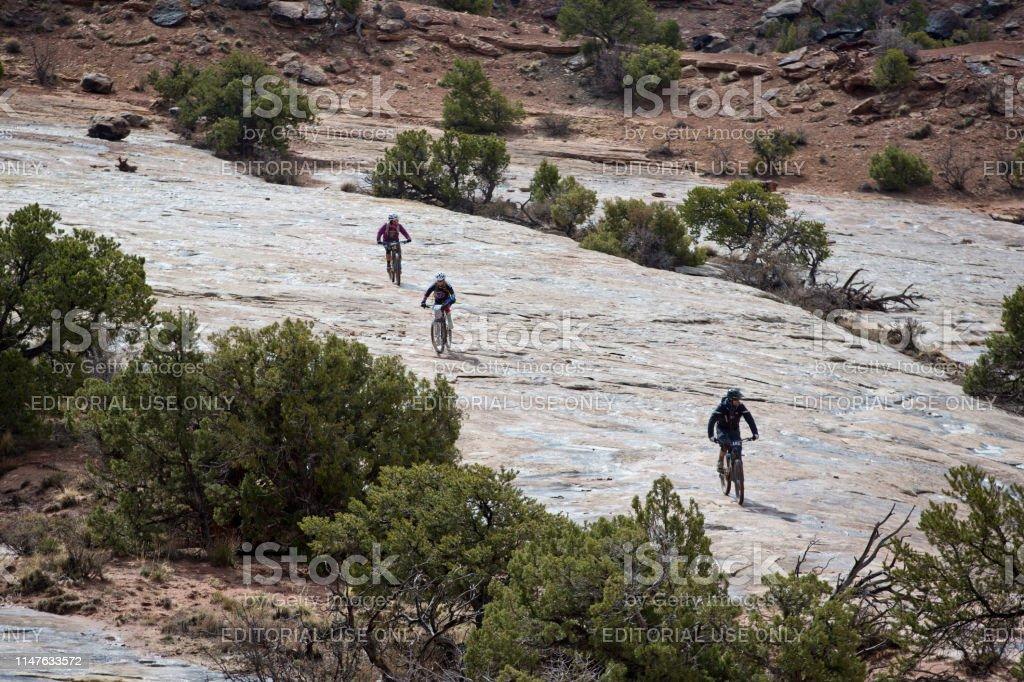 A man leads two women during the Moab Rocks mountain bike race near...