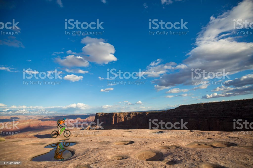A male mountain biker rides a popular trail near Moab, Utah, USA in...