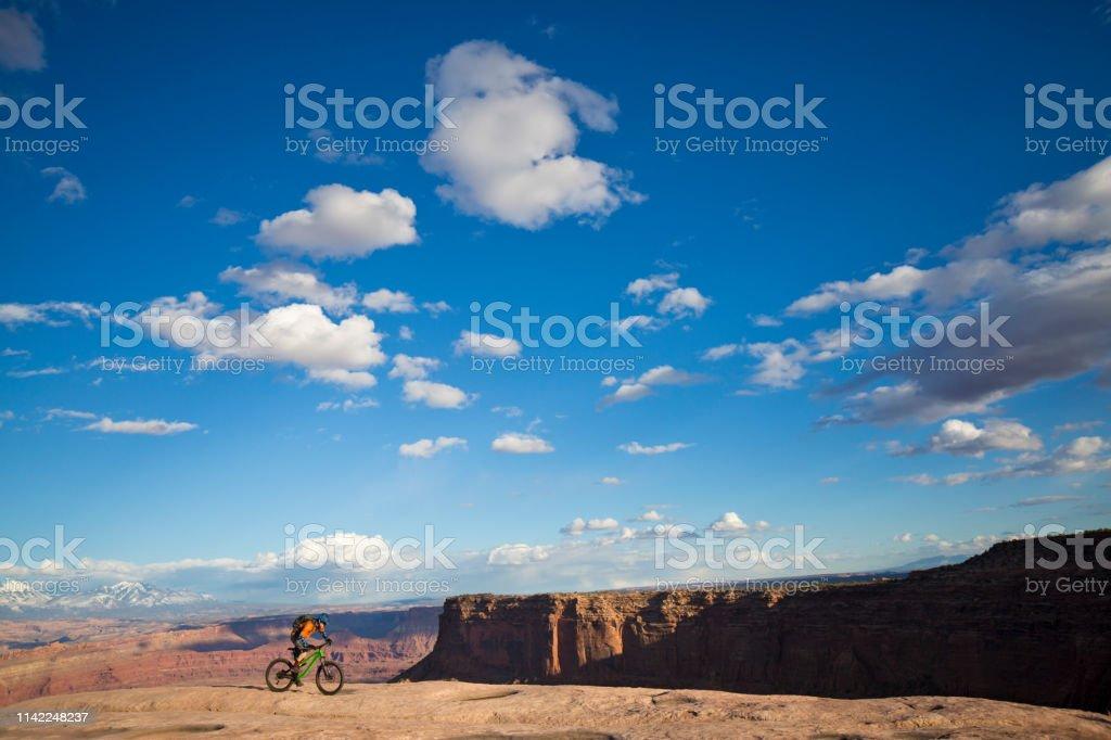 A male mountain biker rides a trail near Moab, Utah, USA in the...