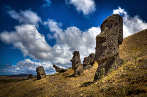 DSLR picture of Moais at the Easter Island in Chile. Moais are human figures carved by the Rapa Nui people in rock. One Moais is in the foreground and four in the background. The sky is mostly sunny with clouds.