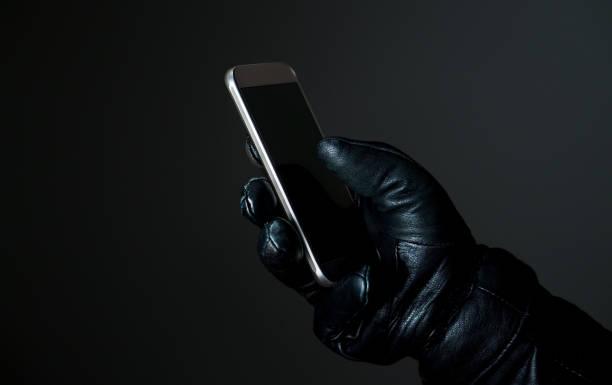 concepto de hilo de seguridad móvil y cibernética. penal con smartphone con guantes de cuero negro en la oscuridad. hacker de teléfono inteligente de pantalla táctil. - robo de identidad fotografías e imágenes de stock