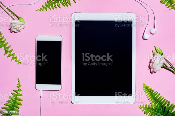 Photo of Mobile and digital tablet on pink