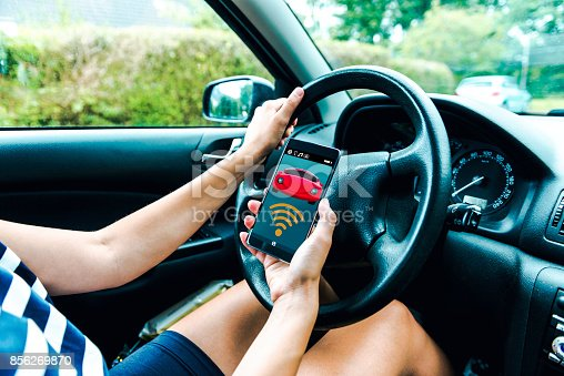 istock Mobile app connects wirelessly to car as women sits in the driver seat 856269870