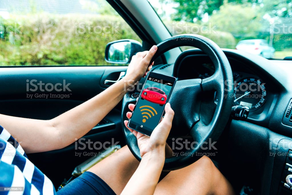 Mobile app connects wirelessly to car as women sits in the driver seat stock photo