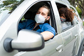 istock Mobile application driver taking a passenger to their destination is wearing face masks to prevent COVID-19 1282421168