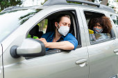 istock Mobile application driver taking a passenger to their destination is wearing face masks to prevent COVID-19 1282421216
