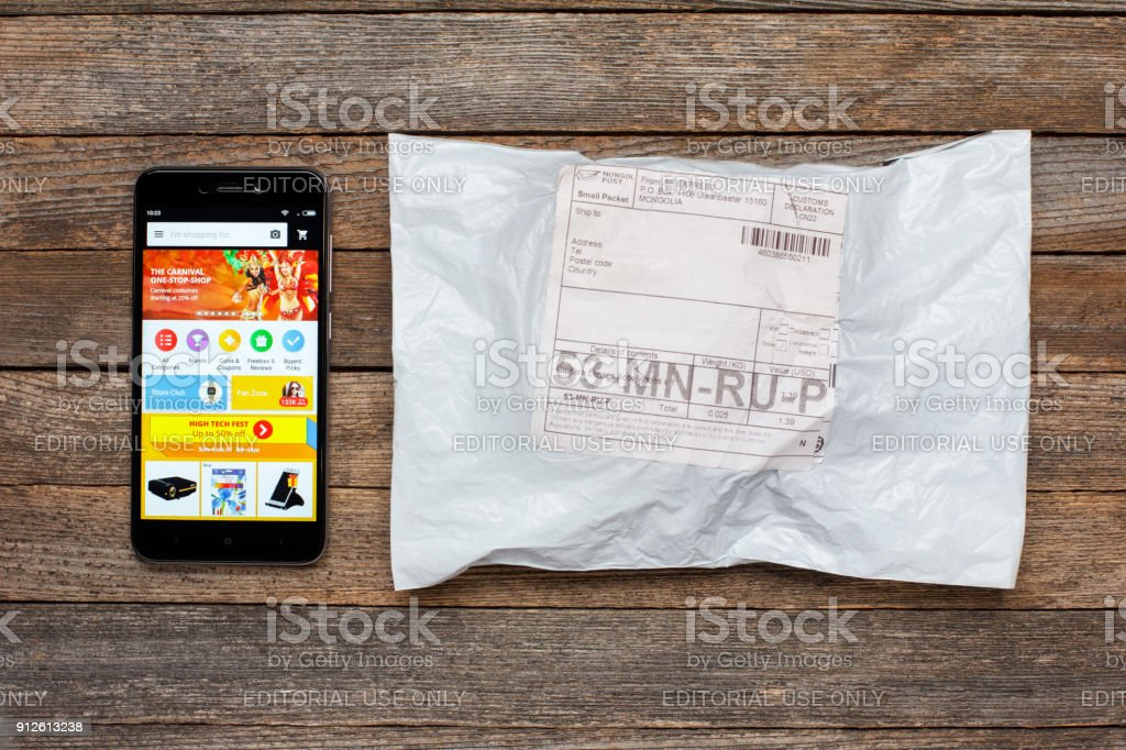 mobile application of the Chinese online store ali express on the screen of the smartphone xiaomi and package parcel on the wooden table stock photo