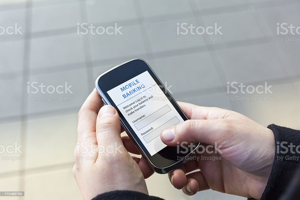 Close up of a human hand holding smart phone with Mobile Banking App...