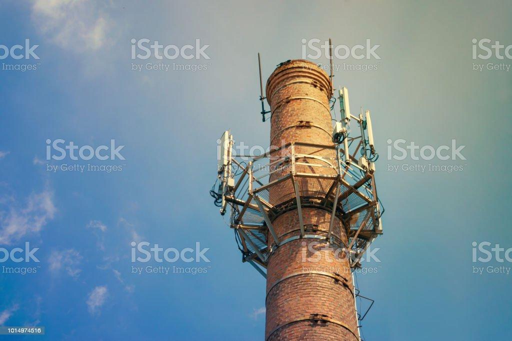 Émetteurs de communication mobile 4 5 sur une conduite de brique ronde sur un fond de ciel bleu avec la lumière du soleil. Pylônes d'antennes de téléphonie mobile communication - Photo