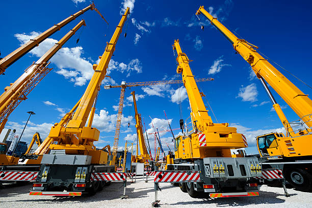 Mobile construction cranes Mobile construction cranes with yellow telescopic arms and big tower cranes in sunny day with white clouds and deep blue sky on background, heavy industry  construction machinery stock pictures, royalty-free photos & images