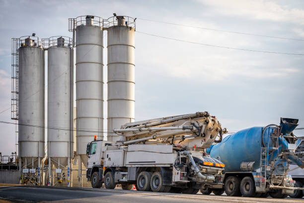 Mobile crane and concrete trucks in front of cement factory Mobile crane and concrete trucks in front of cement factory on highway construction S7, Naprawa, Poland mobile crane stock pictures, royalty-free photos & images