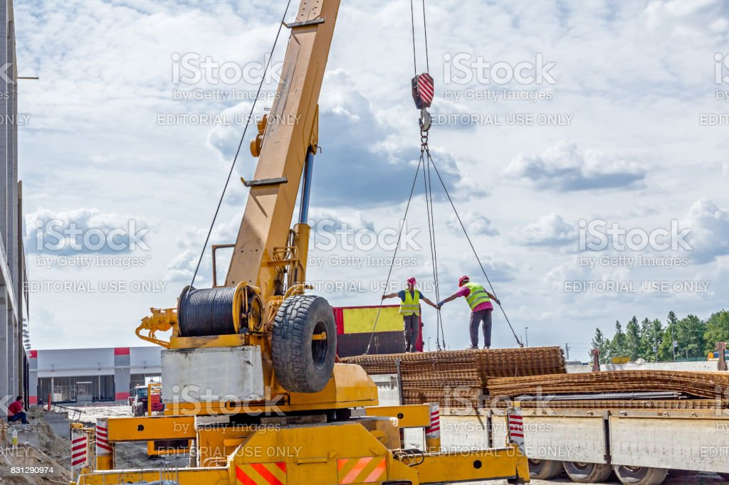 Mobile crane is carry pile of concrete armature, rusty square reinforcement stock photo