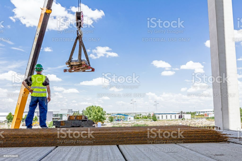 Mobile crane is lifting cargo on pallet stock photo