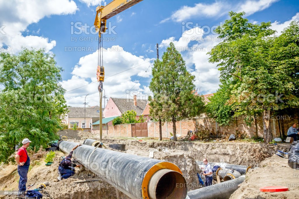 Mobile crane is managing and pulling huge pipe in the trench stock photo