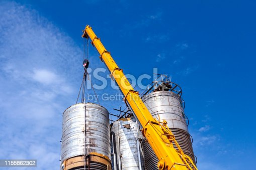 Crane is carry and keeps balance with heavy metal silo in industrial complex.
