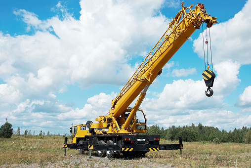 Mobile crane with its boom risen outdoors