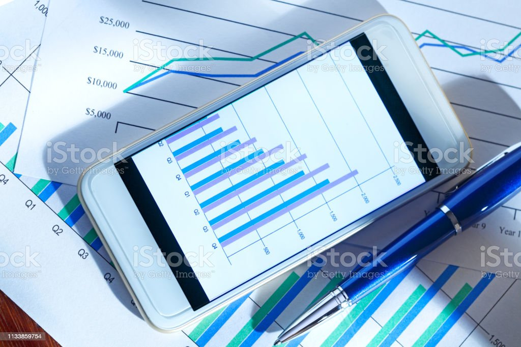 Mobile Device With Bar Chart On Screen Sitting On Desktop stock photo