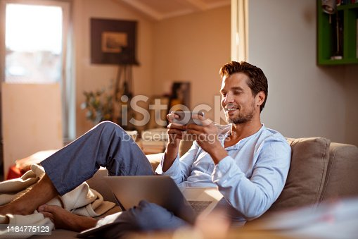 Close up of a young man playing mobile games in the morning