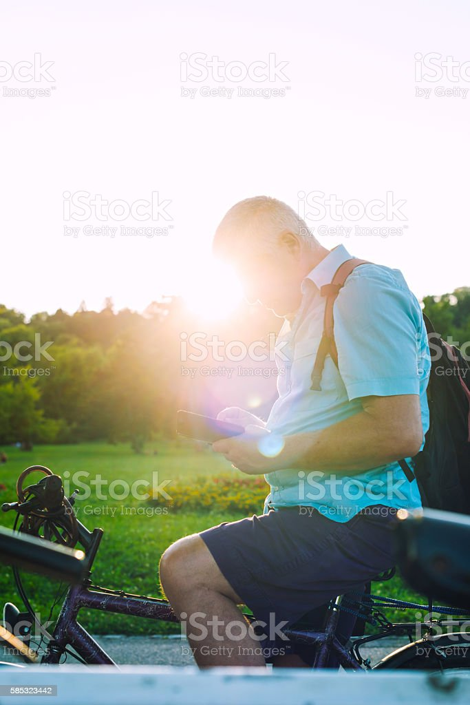 Mobile gaming on bike in the park stock photo