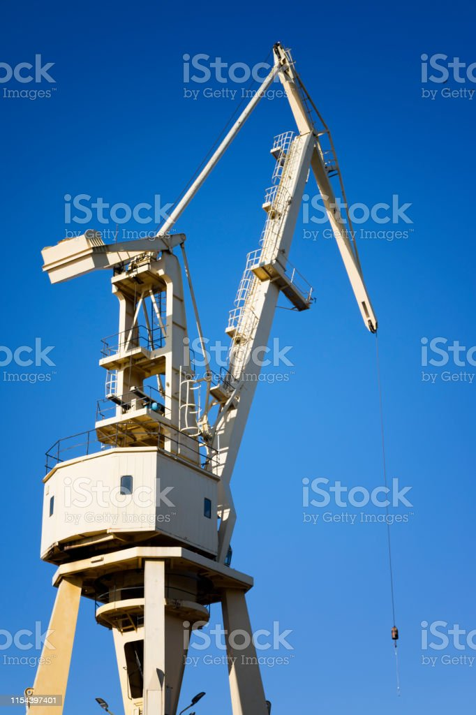 Harbor cranes over blue sky. Transport and technology concept