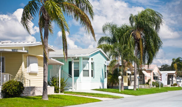 Mobile Home Neighborhood Mobile home park neighborhood in the tropics. Row of manufactured homes. Street view. trailer park stock pictures, royalty-free photos & images
