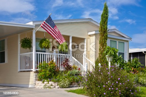 Mobile home with flower garden, front porch, and American flag. Vacation home or retirement home.
