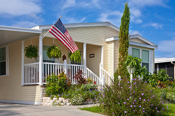 Mobile Home Mobile home with flower garden, front porch, and American flag. Vacation home or retirement home. caravan photos stock pictures, royalty-free photos & images