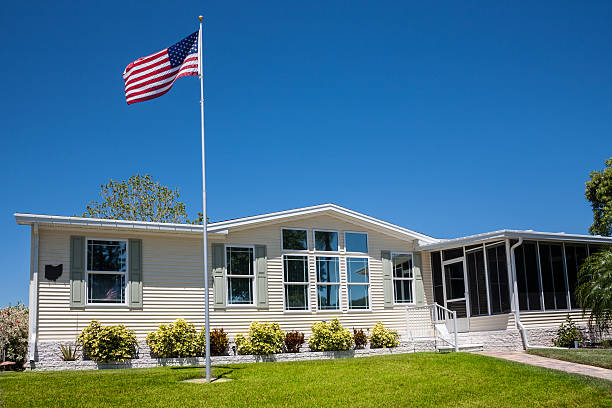 Mobile Home with American Flag Mobile home with American flag, front lawn and clear blue sky. caravan photos stock pictures, royalty-free photos & images