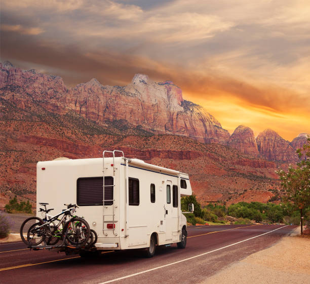 Mobile home with bicycles on Road trip Highway road with motor home at sunset motor home stock pictures, royalty-free photos & images