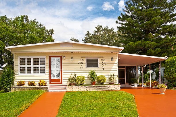 A mobile home with car port and grassy garden Mobile home located in a trailer park. Front yard, driveway and sidewalk. Manufactured home; static caravan. manufactured housing stock pictures, royalty-free photos & images