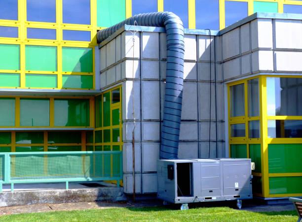mobile industrial air conditioning unit with big flex hose attached to modern building exterior - ambient temperature imagens e fotografias de stock