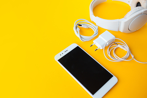 Mobile kit with smartphone, headphones and chargers. Yellow background, Copy space to the left