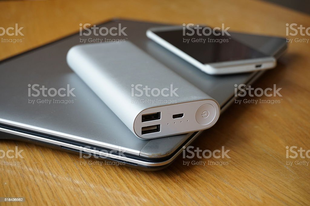 Mobile office with aluminum laptop, cell phone and external battery stock photo