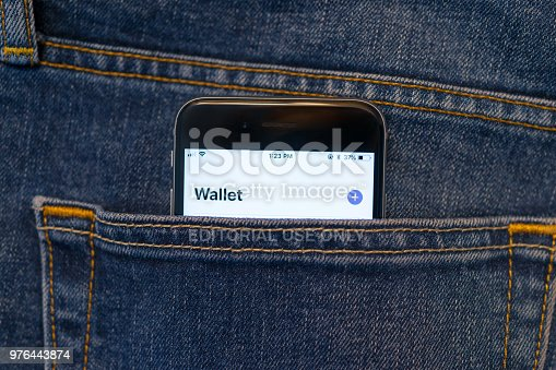 Beijing, China - June 6, 2018: Mobile phone in a denim jeans back pocket. The phone shows a Wallet App display.