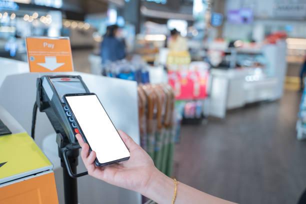 Concepto de pago móvil, cierre la mano sosteniendo el teléfono inteligente con espacio de copia de pantalla blanca para la publicidad, pagando por teléfono inteligente a través de la máquina de pago automático en el supermercado. Quiosco de pago de a - foto de stock