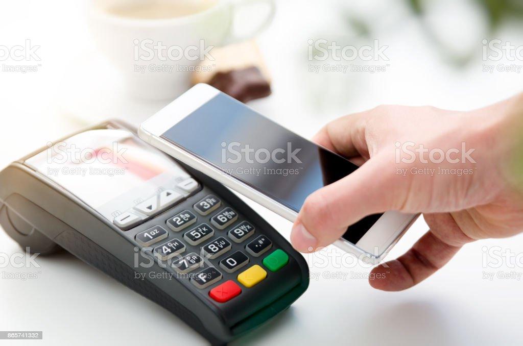 Pago por móvil en café con teléfono inteligente - Foto de stock de Aire libre libre de derechos