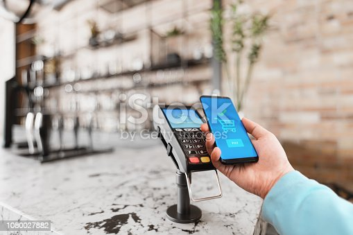 Man holding smartphone to the counter-top payment terminal for mobile payment in a cafe.