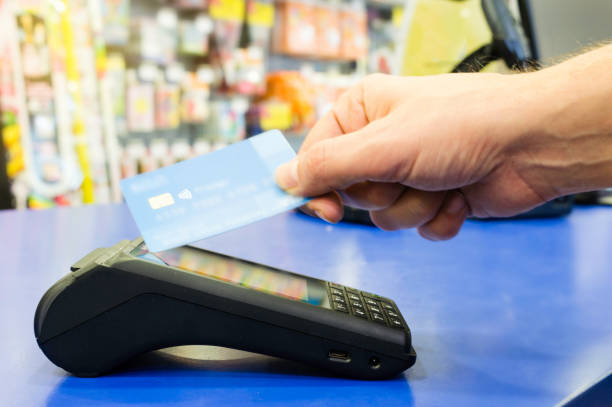 mobile payments concept. customer is paying using wireless or contact-less credit card and payment terminal with nfc technology - paying with card contactless imagens e fotografias de stock