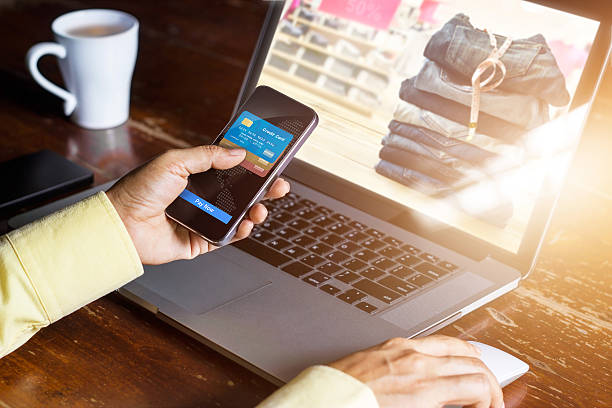 Mobile payments, Man using smartphone  shopping online Mobile payments, Man using smartphone  shopping online, laptop screen showing products for customers. home shopping stock pictures, royalty-free photos & images