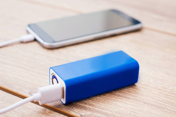 Mobile phone and battery power bank charger on a office desk - foto stock