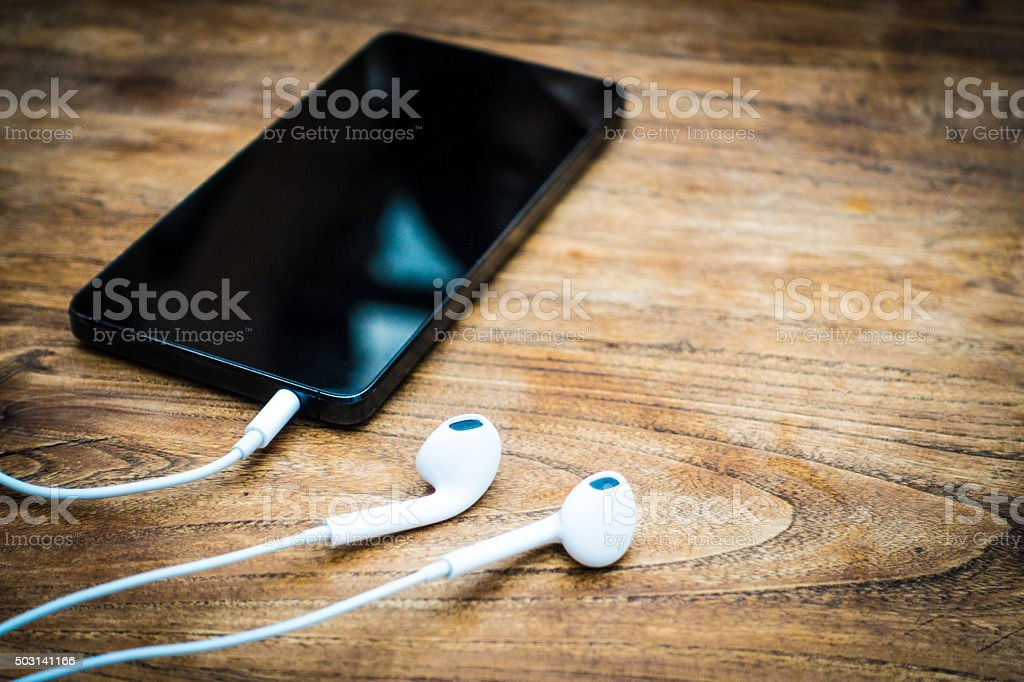Superieur Mobile Phone And Headphones Lay On Wooden Table Stock Photo