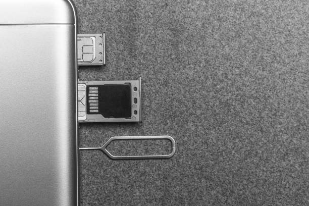 mobile phone and open slots for nano sim cards, micro sd drive and metal key on grey background with copy space, black and white photo - memory card stock photos and pictures