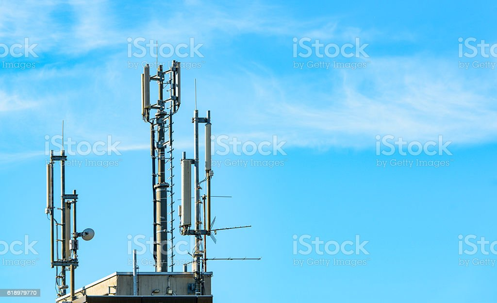 Mobile phone antennas on rooftop  against blue sky stock photo