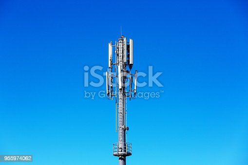 Clear blue sky provides copy space behind a cell phone mast.