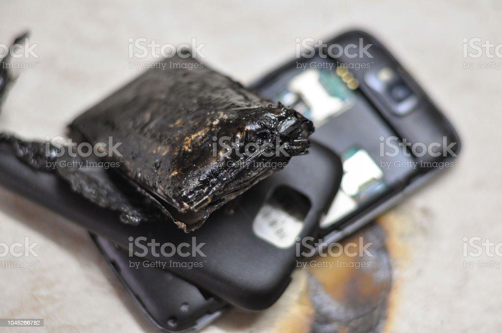 Mobiltelefon batteri exploderar och brännskador på grund av överhettning bildbanksfoto