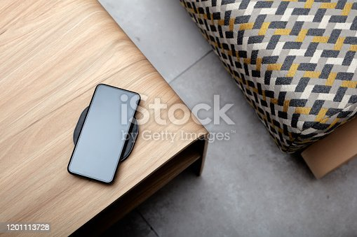 A mobile phone charging wirelessly is on a wooden table,Vertical shooting of mobile phone wireless charging scene, background with wood desktop and cloth sofa,