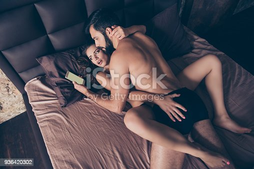 494388938istockphoto Mobile phone, cheating anf jealousy concept. Young gorgeous lover lady is shocked, she saw her man looking at the phone while having prelude in  bed 936420302