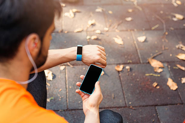 Mobile phone connected to a smart watch - foto de acervo